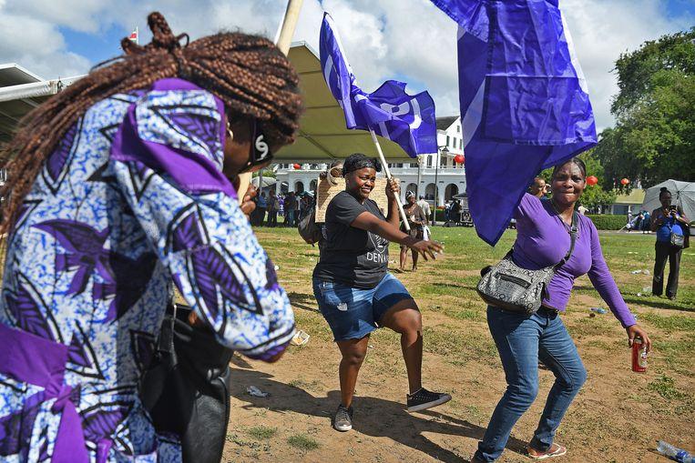 Aanhangers van de NDP, de partij van president Desi Bouterse, dansen op het Onafhankelijkheidsplein om hun leider te steunen tijdens zijn proces voor de Krijgsraad. Beeld Guus Dubbelman / de Volkskrant