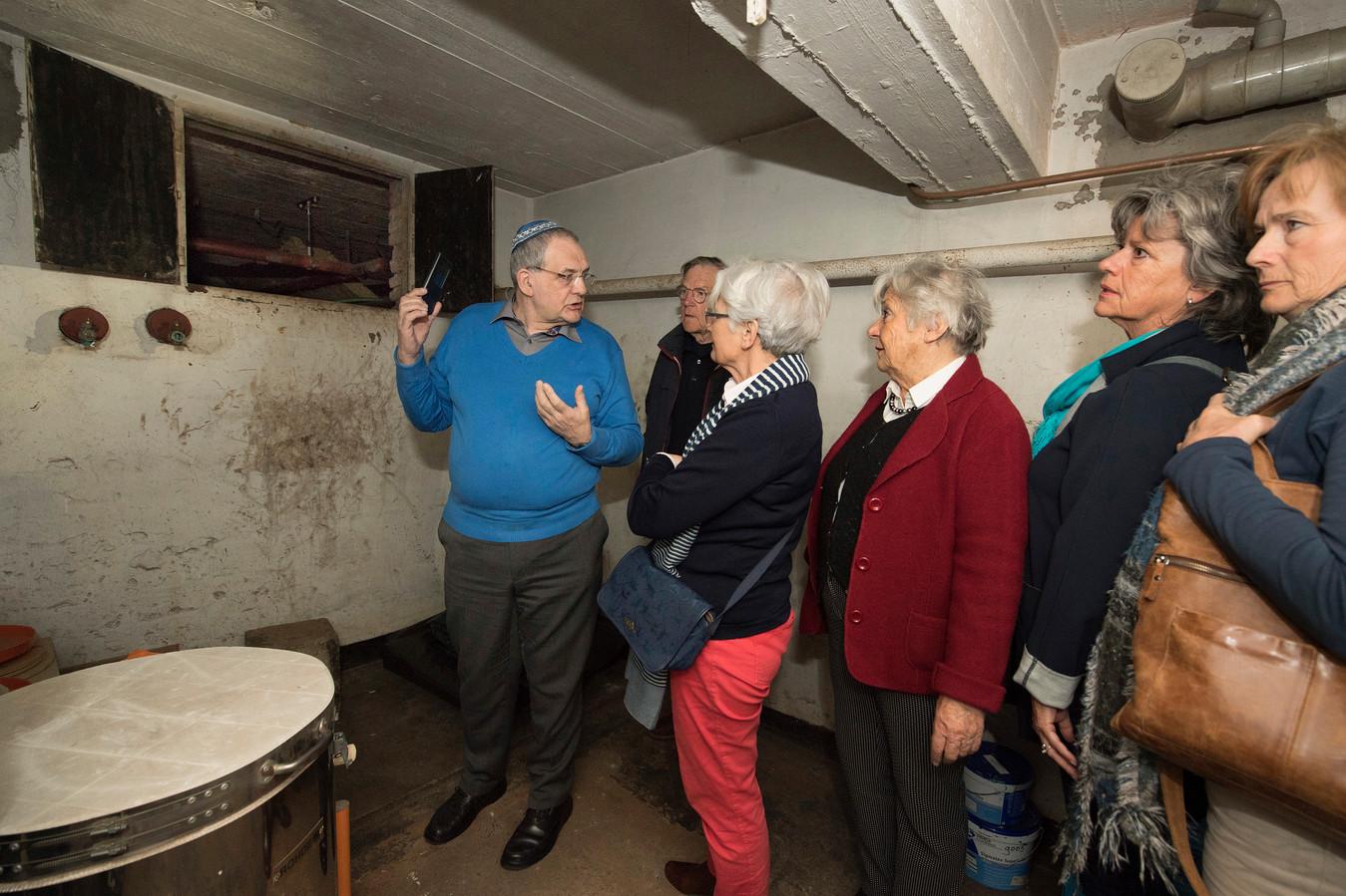Joop van Dijk laat bezoekers de schuilplaats van 2 Joodse families zien in de kruipruimte van de Beekmanschool.
