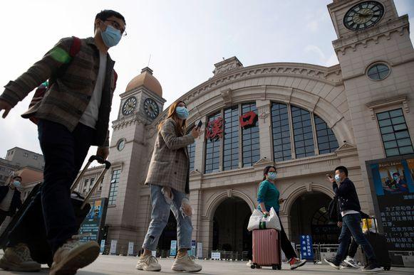 Chinezen uit Wuhan reppen zich naar het treinstation Hankou om de miljoenenstad te verlaten na meer dan twee maanden lockdown.