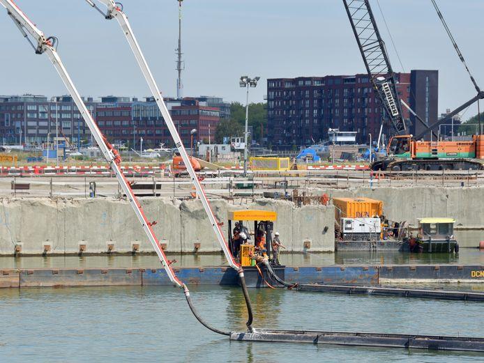 Met lange witte slurven wordt het beton tot op 22 meter onder NAP gepompt in het toekomstige buitenhoofd van de Nieuwe Sluis, het oranje karretje op de balk rijdt heel langzaam heen en weer om de beton gelijkmatig te verdelen.