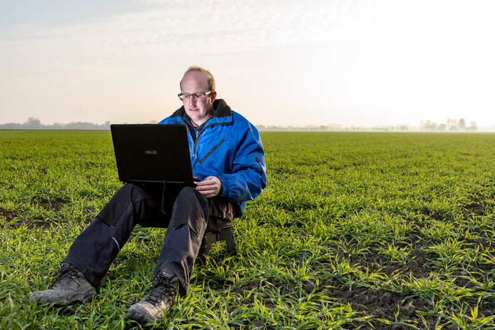 Mark Verhage uit Oostburg checkt data op een veld met wintergerst.