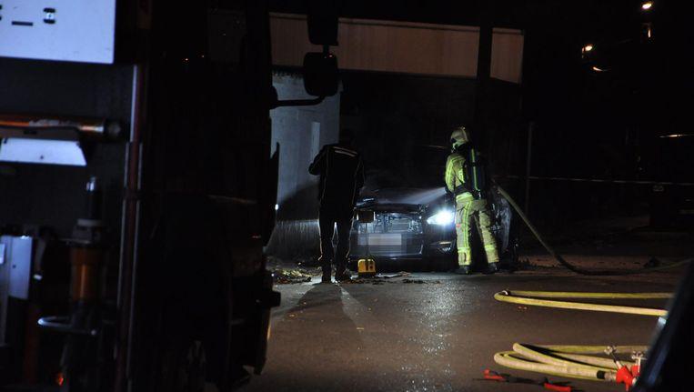 De brandweer is de brand in de auto aan het blussen.