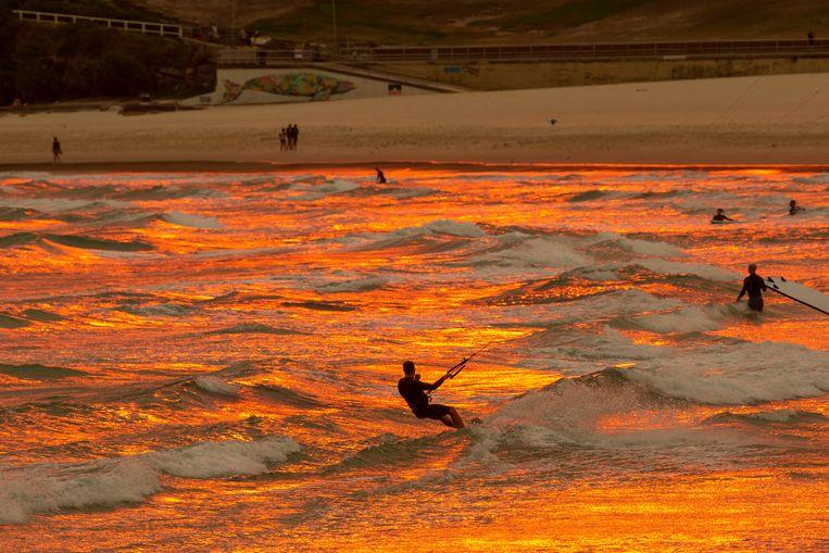 Terwijl de temperatuur steeg naar begin veertig graden en de noodtoestand werd uitgeroepen, zochten surfers verkoeling bij Bondi Beach in Sydney.  Beeld Getty Images