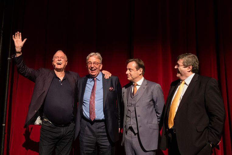 John Cleese omarmt Antwerps Voka-directeur Luc Luwel. Bart De Wever en Voka-voorzitter Jo De Backer kijken geamuseerd toe.
