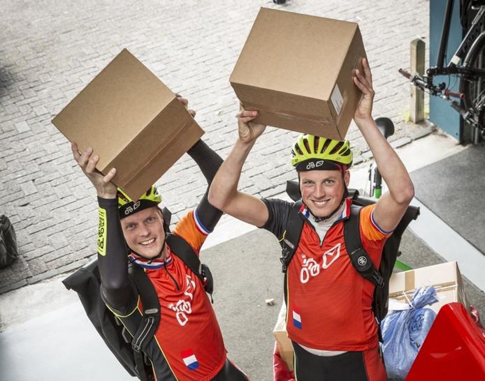 Fietskoeriers Dennis van Compayen (links) en Robert de Vries verzamelen morgen Oranje-cadeaus. Foto: Henri van der Beek