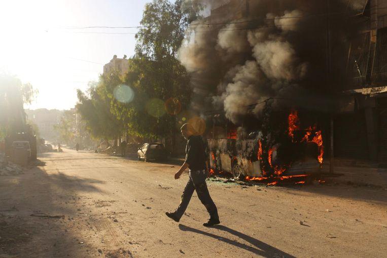 Een man loopt naast een brandende bus in de wijk Salahaddin in Aleppo. Beeld afp