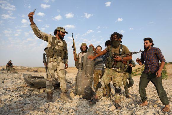 Jihadisten poseren trots met de restanten van het vliegtuig.