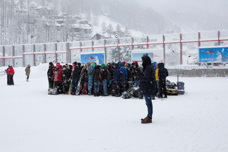 Wintersporters staan in de rij te wachten op een vlucht met de helikopter naar Täsch.