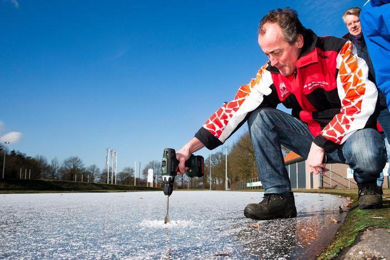 IJsmeester Jaap in 't Veld meet de ijsdikte voor de eerste schaatsmarathon op natuurijs bij schaatsclub IJSCH in Haaksbergen. Beeld anp