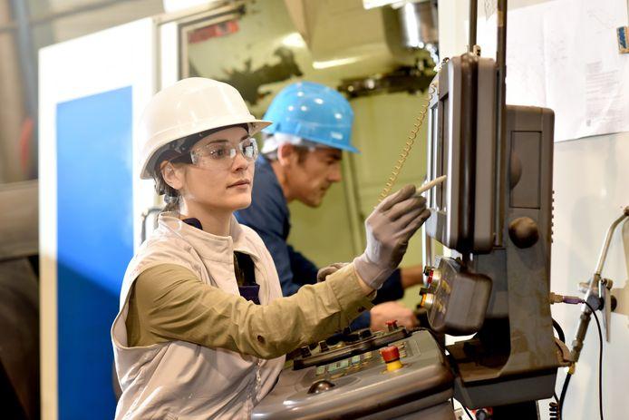 Een man en een vrouw aan het werk in een fabriek. Beeld ter illustratie.