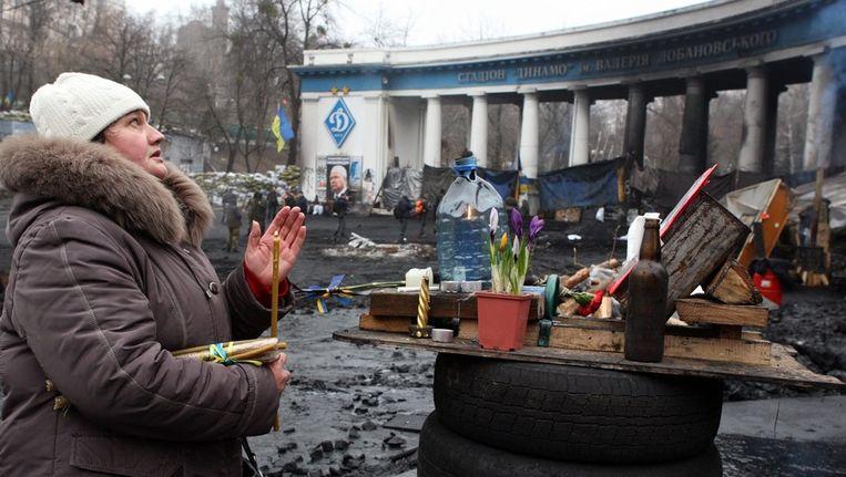 Een Oekraïense vrouw bij een monument op de barricades in Kiev. Beeld epa