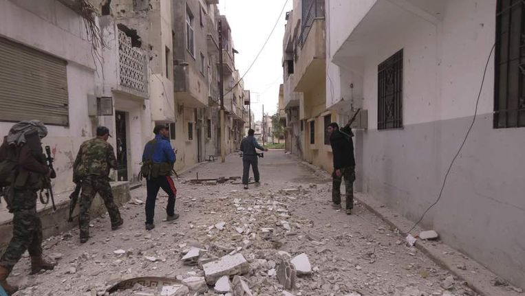 Leden van het Vrije Syrische Leger lopen in de stad Homs. Beeld reuters