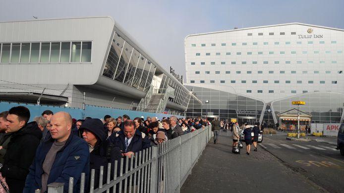 De passagiers die met de bus mee moeten, staan buiten bij de aankomsthal in een lange rij te wachten.