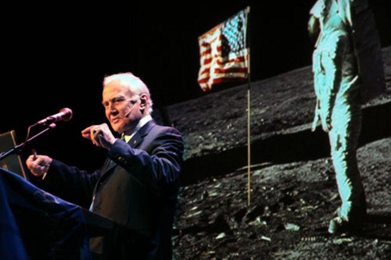 Edwin Aldrin spreekt in Delft zijn gehoor toe met op de achtergrond een foto van hem als astronaut op de maan. (Najib Nafid - de Volkskrant) Beeld