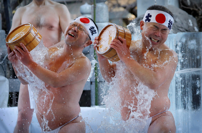 Japanse mannen gooien ijskoud water over zich heen tijdens de jaarlijkse koudwater-uithoudings-ceremonie in Tokio. Hiermee zuiveren ze hun ziel en roepen ze geluk op in het nieuwe jaar. Foto Kim Kyung-Hoon