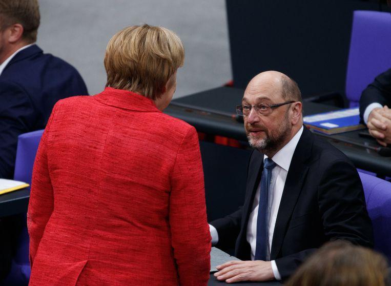 Angela Merkel (op de rug gezien) en Martin Schulz deze week in het Duitse parlement.  Beeld EPA