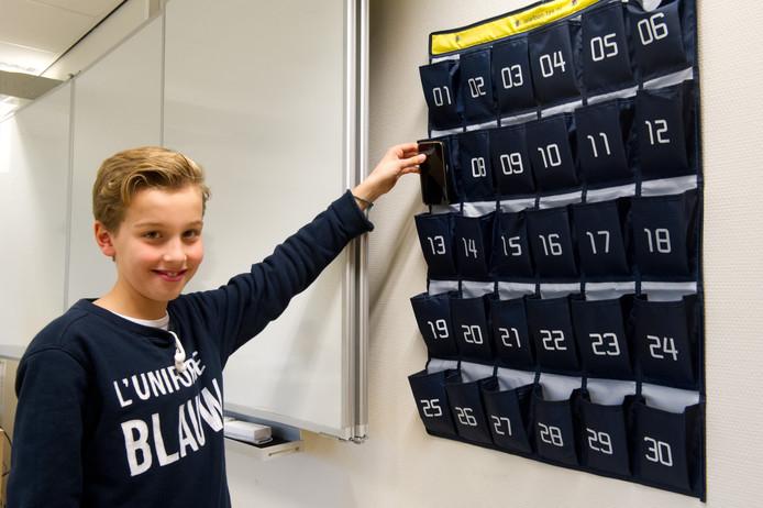 Boaz de Jonge (13) stopt zijn telefoon in de tas aan het begin van de les. Hij heeft cijfertje 8.