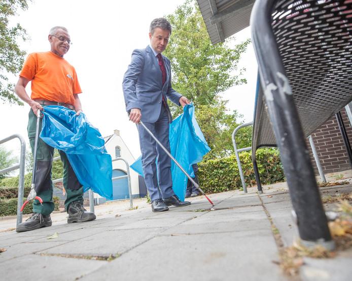 Burgemeester Huub Hieltjes van Kapelle ruimt zwerfvuil op met een medewerker van de Betho.