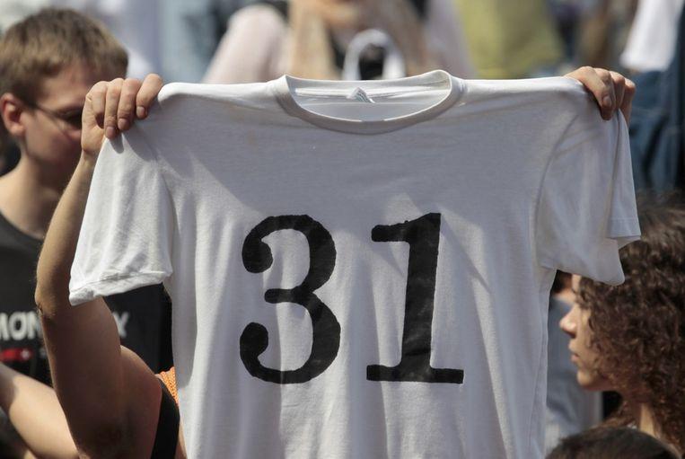 Een demonstrant houdt een t-shirt omhoog met het cijfer 31, verwijzend naar artikel 31 uit de Russische grondwet. Volgens dit artikel hebben Russen het recht zich te verzamelen. Beeld reuters