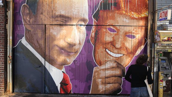 Een muurschildering in New York van Poetin die een masker van Trump vasthoudt.