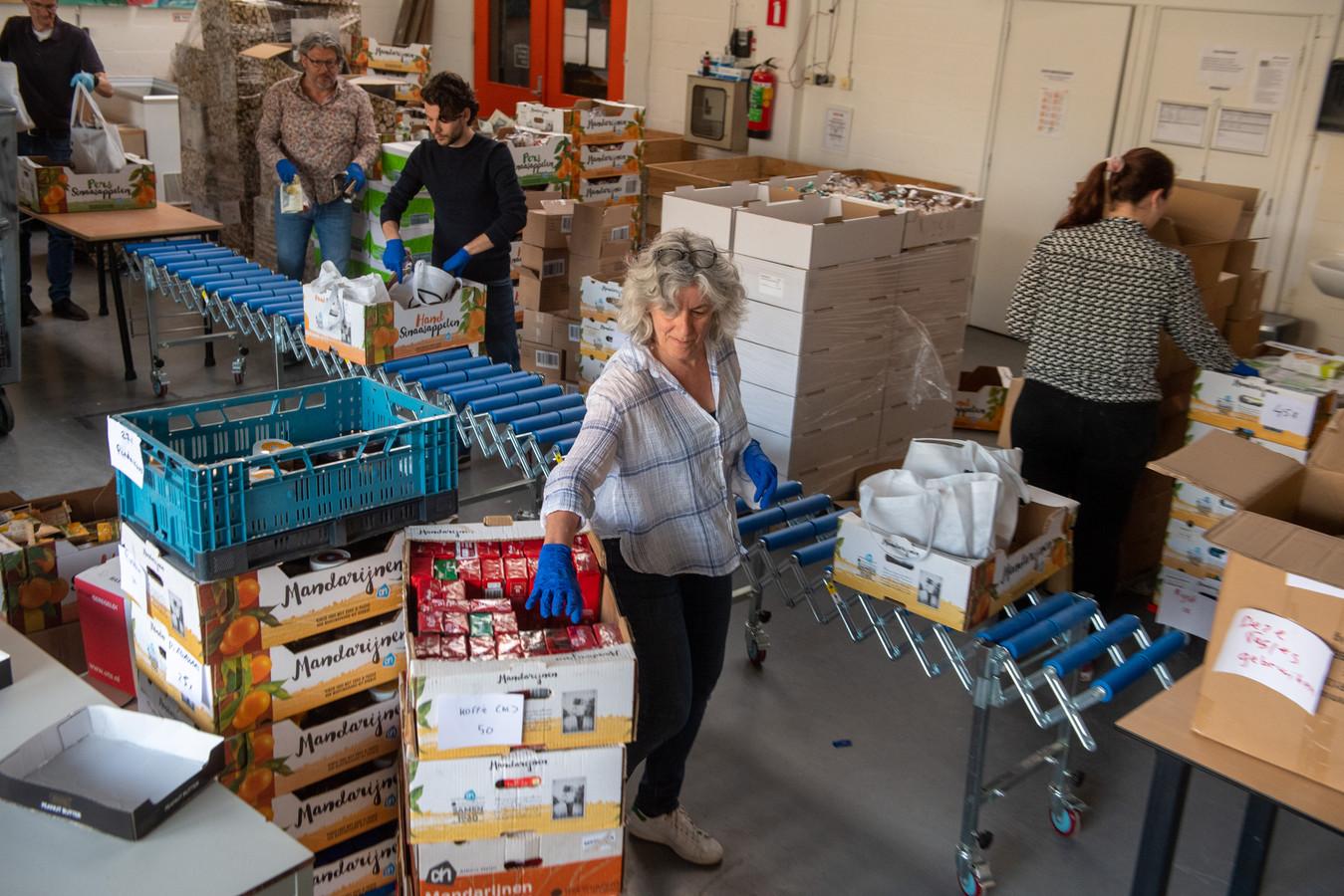 Vrijwilligers van de voedselbank pakken voedselpakketten in voor de klanten. Ze krijgen door de coronacrisis steeds meer aanmeldingen.