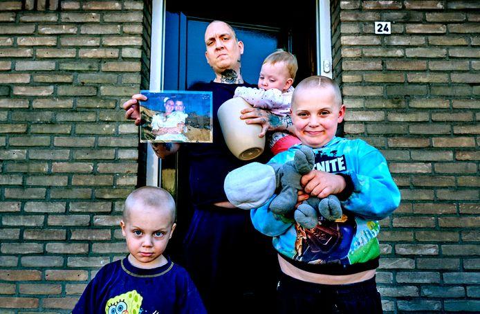 Ricardo Legen met hun drie kinderen Jailey (1), Damon (3) en Lucas (7). In zijn handen een trouwfoto en de urn met de as van zijn overleden vrouw Hennie.
