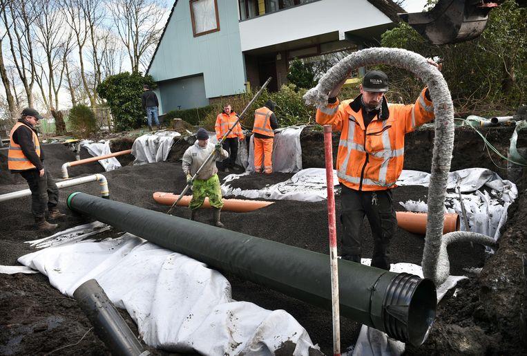 In Kockengen wordt nieuwe riolering en drainage aangelegd zodat het water voortaan gemakkelijker kan worden afgevoerd. De gemeente hoogt ook de voortuinen op. Beeld Marcel van den Bergh