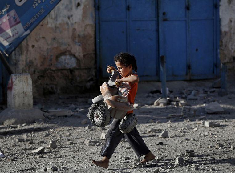 Een kind redt zijn tractor uit de puinhopen van een verwoest huis. Beeld ap