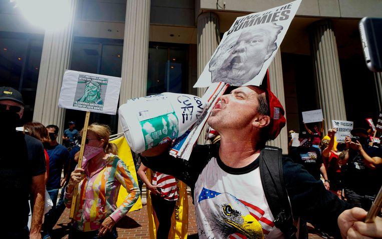 Een demonstrant met een anti-Trumpbord doet alsof hij uit een fles bleekmiddel drinkt, omdat Trump suggereerde dat dit middel zou kunnen helpen tegen corona. Beeld AFP