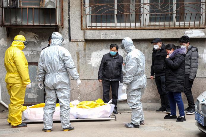 Begrafenisondernemers halen een slachtoffer van het coronavirus op in Wuhan. e