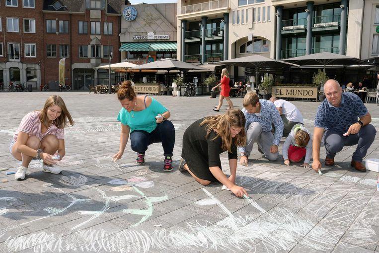 De kandidaten en kinderen tekenen bloemen en bomen op de grijze stenen.