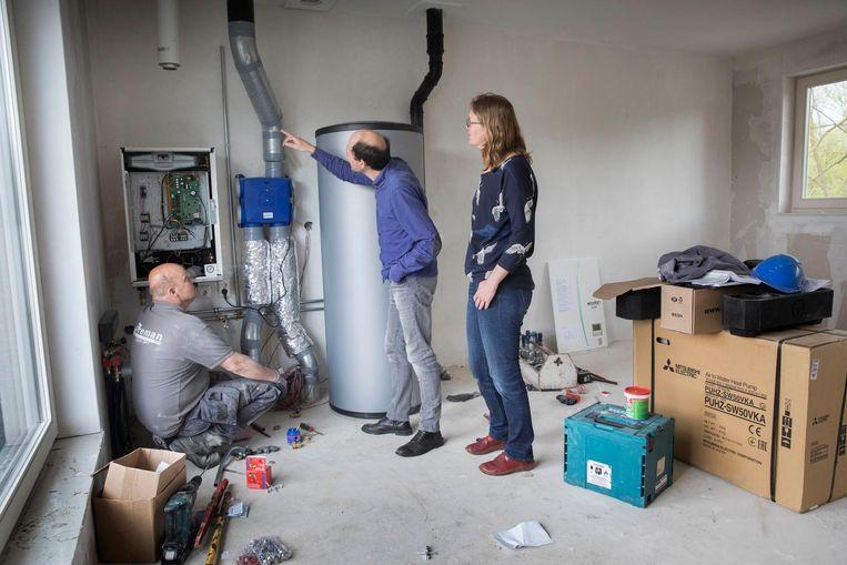 Een installateur is bezig met het aansluiten van de warmtepomp. Beeld Werry Crone/HH