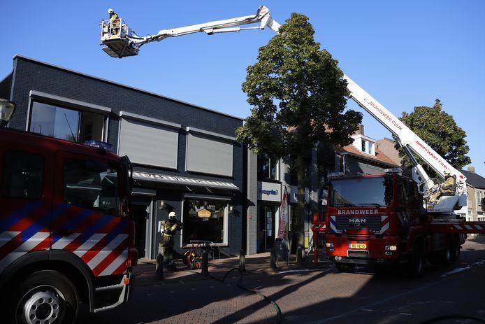 De brandweer blust de brand in het cafetaria aan de Molenstraat in Cuijk.