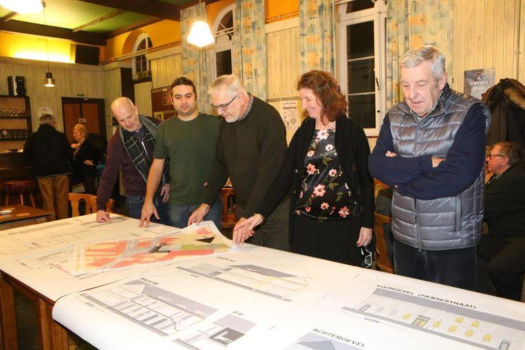 Geïnteresseerden bekijken de bouwplannen van het parochiecentrum.