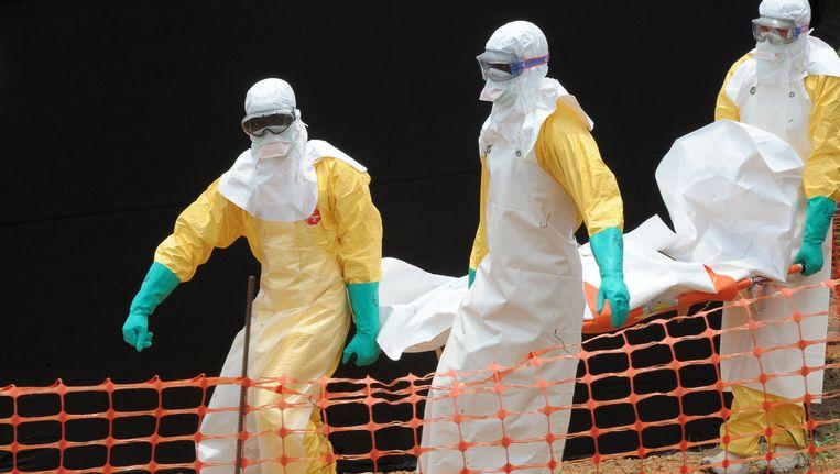 Medewerkers van Artsen Zonder Grenzen' dragen het lichaam van een van de slachtoffers van het ebolavirus in Sierra Leone.
