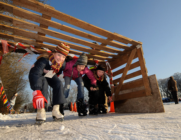 Drie meisjes duiken onder een nagemaakt 'Elfstedenbruggetje' door op de ijsbaan in Zenderen.