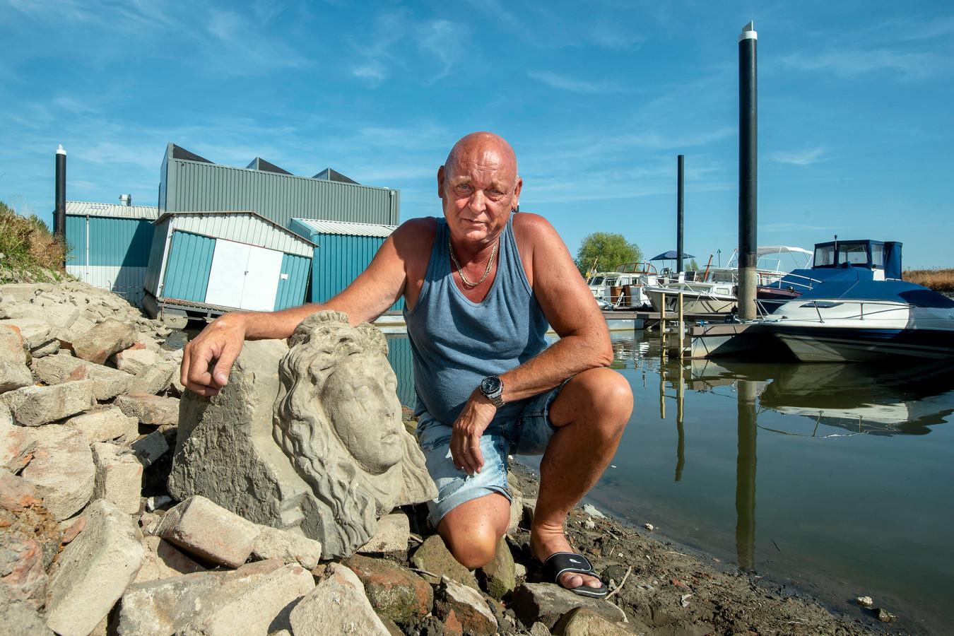 Jelle van der Meer bij het stenen hoofd dat hij ontdekte bij de jachthaven van Roei- en Zeilvereniging Jason in Arnhem.