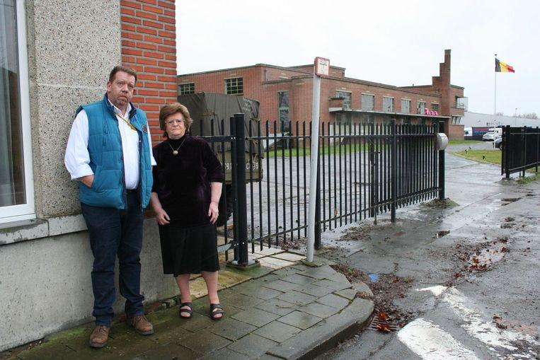Yves Stouthuysen en Simone Christiaens waar vroeger het café was. Op de achtergrond het huidige Quattro, voormalige schrijnwerkerij van de fabriek, en daarachter ABInBev op de vroegere fabriekssite.