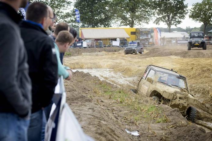 Toeschouwers tijdens Budel Offroad kijken toe hoe een terreinwagen door de modder ploegt. foto Jean Pierre Reijnen/fotomeulenhof