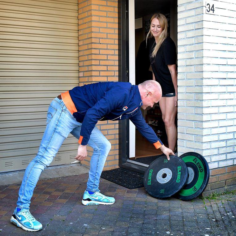 Performance coach Auke Klarenbeek levert gewichten af bij handbal international Lois Abbingh in Emmen, zodat zij thuis kan trainen. Beeld Klaas Jan van der Weij