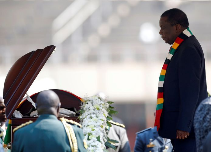 Zimbabwaanse President Emmerson Mnangagwa groet de kist van de overleden president Mugabe.