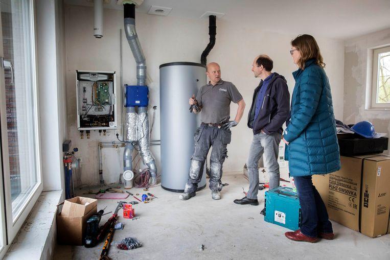 Evert Hassink en Claudia Holstein gaan gasloos wonen. Installateur Hans van der Kamp is bezig met het aansluiten van de pompinstallatie. In het midden de boiler van 300 liter. Beeld Werry Crone