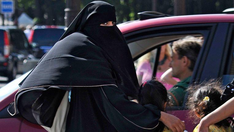 Vrouw gehuld in een niqab haalt in Parijs haar dochtertjes van school. Ook de niqab valt onder het verbod. Beeld EPA