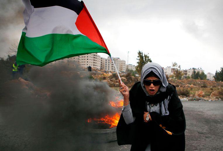 Een vrouw zwaait met een Palestijnse vlag in Ramallah. De afgelopen dagen waren er veel protesten in de regio als reactie op het besluit van de Amerikaanse president Donald Trump om Jeruzalem te erkennen als hoofdstad van Israël.  Beeld AFP