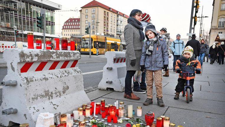 Een Duits jongetje kijkt naar een klein monument nabij de oudste kerstmarkt van Duitsland, de Striezelkertmarkt in Dresden. Beeld Guus Dubbelman