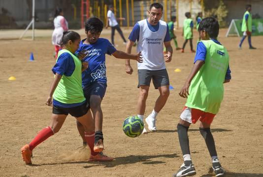 Xavi Hernández (midden) voetbalt met kinderen in Mumbai.