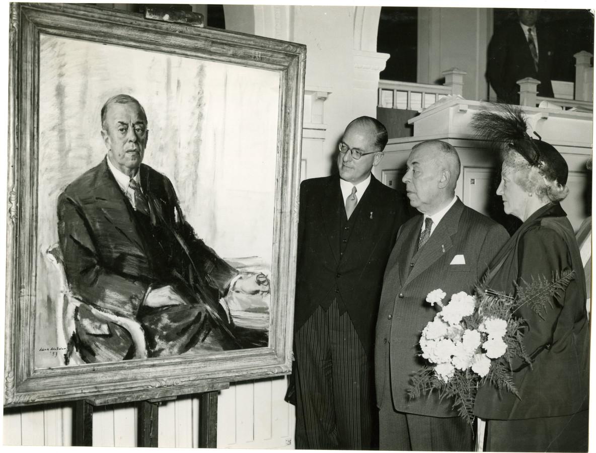 Wethouder Louis Feber (volkshuisvesting) kijkt naar een schilderij van zichzelf. Hij kreeg dit in 1953. Links burgemeester Frans Schokking van Den Haag.