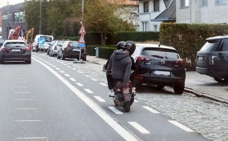 De scooter passeert de flitspaal, aan 60 per uur. De passagier dekt de nummerplaat af met zijn rechterhand.