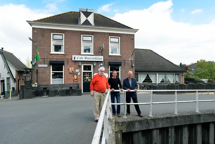 Piet van Rees (l), Arjan Wemmers en Marius Mourik (r) voor café Boerenklaas, waarvan de gevel werd beschadigd door een wiel van het neergestorte vliegtuig.