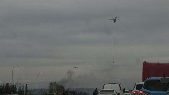 Een helikopter sproeit water om het vuur te blussen.